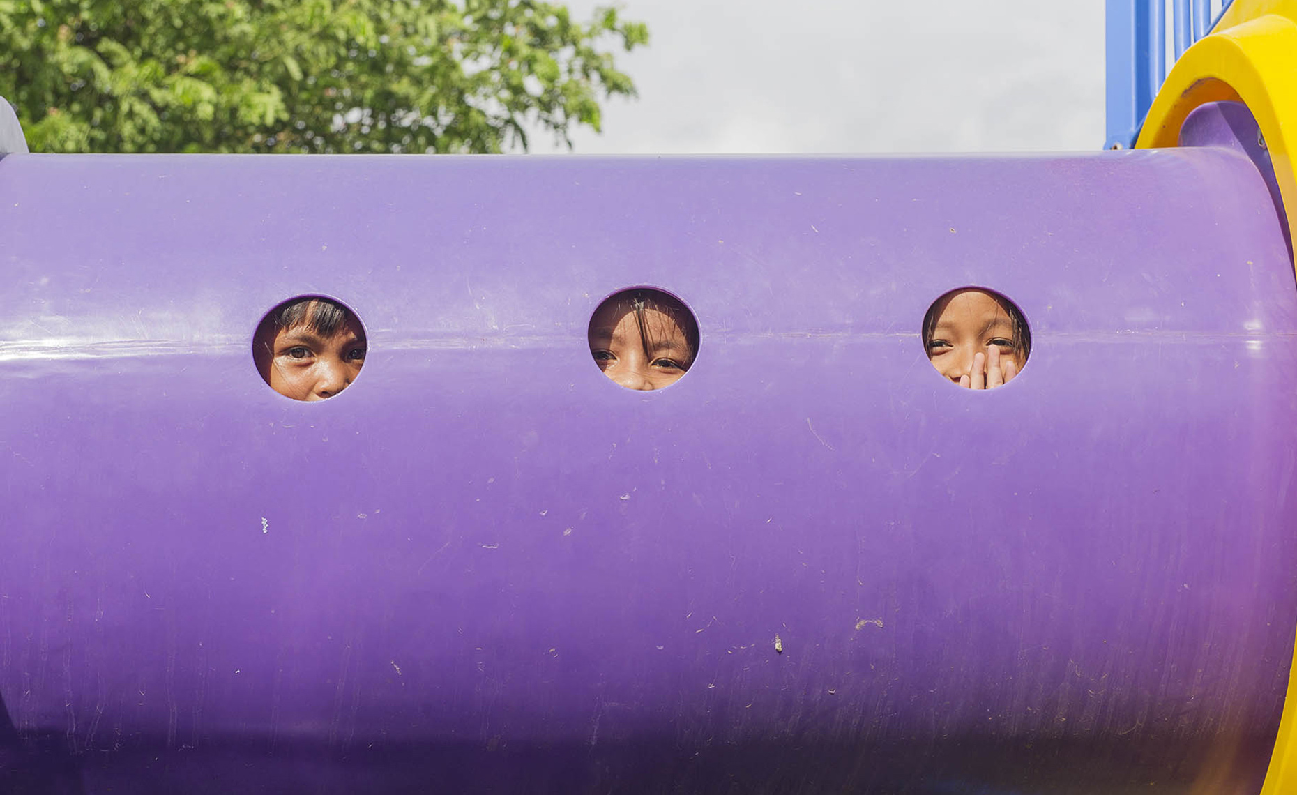 LAT_PhotoReporters_youngsters-peek-from-playground-equipment-at-Sunrise-Childrens-Village_Phnom-Penh_Cambodia