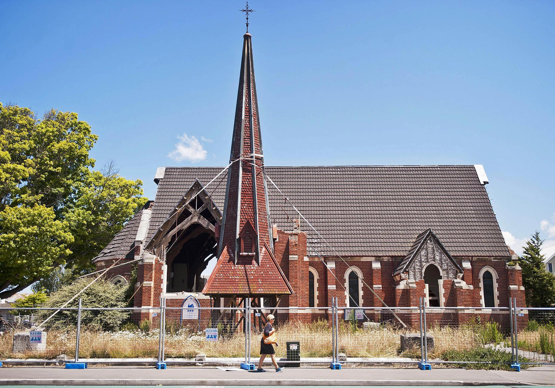 NEW_PhotoReporters_Woman-walks-by-Chinese-Methodist-Church-damaged-in-earthquake_Christchurch_NZ
