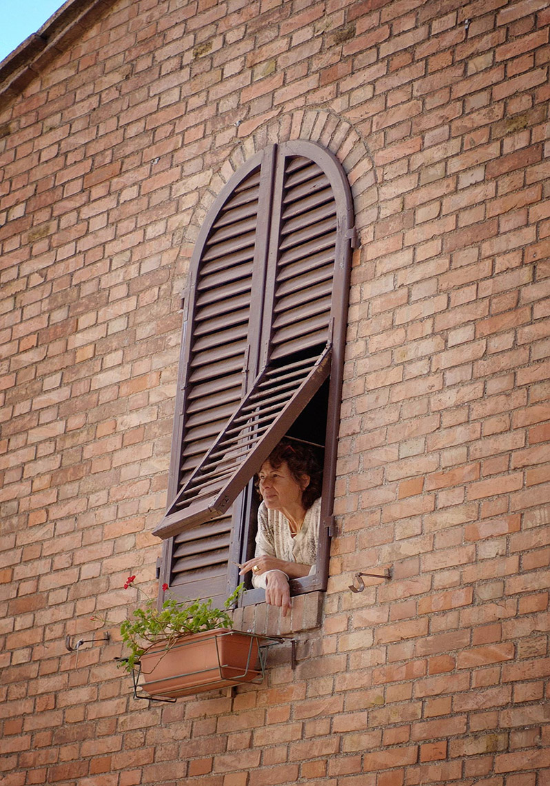 TRA_PhotoReporters_woman-peerfing-from-window_Casole-D-Elsa_Italy